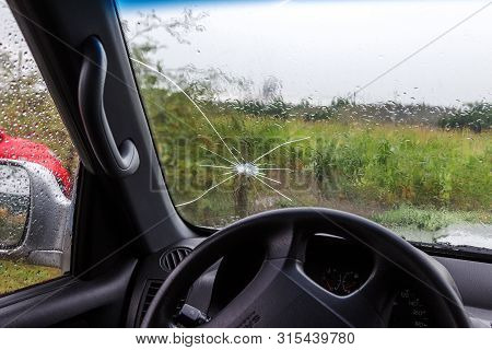 Broken Windshield Of A Car. A Web Of Radial Splits, Cracks On The Triplex Windshield. Broken Car Win