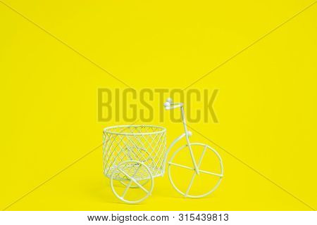 A Toy Bike. The Idea For A Postcard. Yellow Background. Minimalism