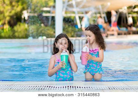 Little Girls In Bright Swimsuits Drink Cocktails Near The Pool On A Sunny Summer Day
