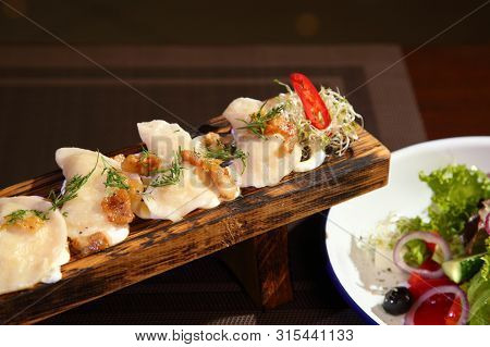 Dumplings With Potatoes And Greaves In Sour Cream On A Wooden Board And Salad. Dumplings With Potato