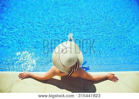 Beautiful  Sexy Woman In Sun Hat Taking Sun Bath Near Swimming Pool.