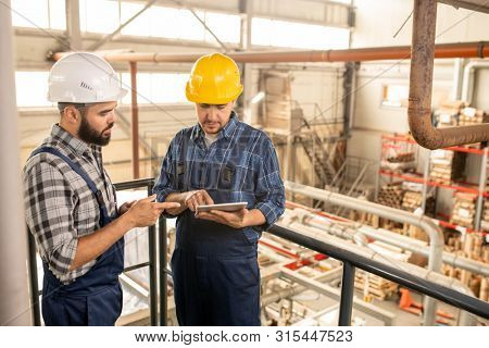Two young engineers of large factory discussing online technical data