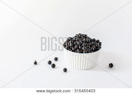 Ripe Black Currant Or Blueberries In A Small White Cup On A White Background. Black Currant Harvest.
