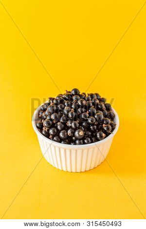 Ripe Black Currant Or Blueberries In A Small White Cup On A Yellow Background. Black Currant Harvest