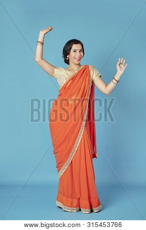 Happy Attractive Young Indian Woman In Sari Dress Dancing On Blue Background