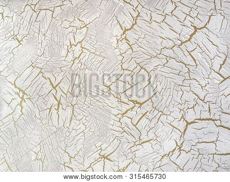 Decorative White Plaster With Aging Effect. Ivory Background With Yellow Cracked Paint. Texture Back