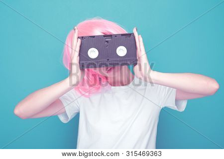 90s Fashion. Girl With Cassette Standing Isolated In A Blue Background.