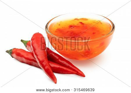 Sweet Chilli Sauce In A Glass Bowl Next To Three Red Chillies Isolated On White.