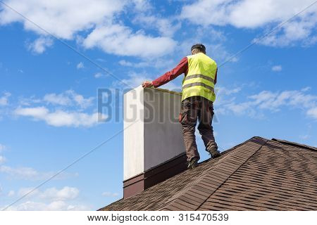 Professional Workman Standing Roof Top And Measuring Chimney Of New House Under Construction Against