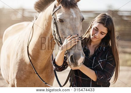 Animals, Friendship And Hobby Concept. Pretty Young Woman In Rural Area Smiling, Gently Petting Hors