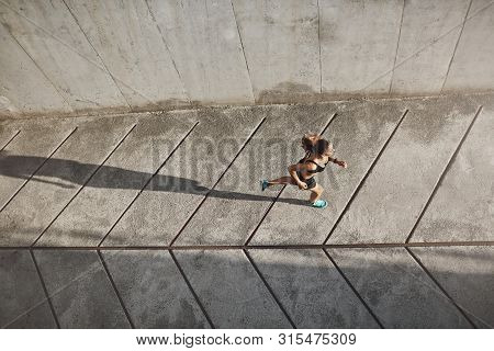 Overhead View Athletic Female Jogger Running On Concrete Track In Black Sportsbra And Shrots, Move T