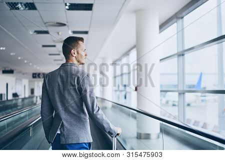Well Dressed Young Man Travel By Airplane. Businessman With Luggage Walking On Travelator At Airport