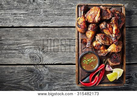 Overhead View Of Jerk Chicken On A Rude Board With Sauce And Lemon On A Rustic Wooden Table, Horizon