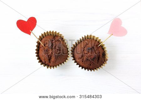 Two Valentine Decorated Cupcakes With Symbols Of Hearts Top View On A Table / For Him And Her