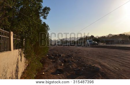 The Road And Part Of The Fence In The Desert Against The Backdrop Of The Egyptian Mountains In The S