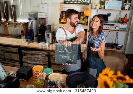 Business owner holding Open Sign. Proud couple opening their store