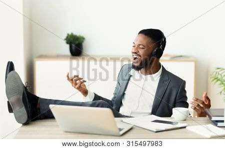 Handsome African Businessman Listening Music Imagining That He Is Rockstar, Putting His Legs On Tabl