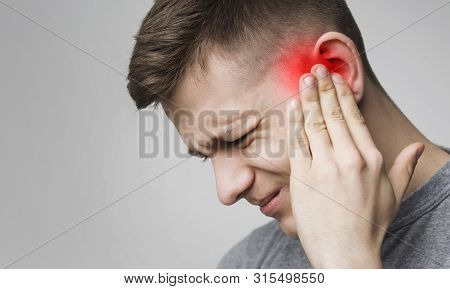 Young Man Has Sore Ear, Suffering From Otitis, Touching His Inflamed Head, Close Up, Empty Space