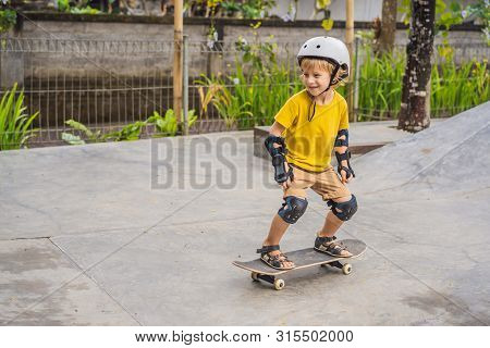 Athletic Boy In Helmet And Knee Pads Learns To Skateboard With In A Skate Park. Children Education,