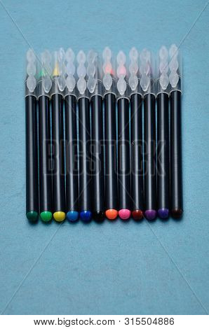 An Assortment Of Color Pens On A Blue Background