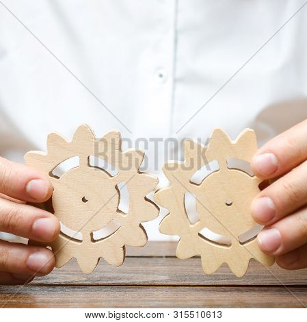 Businessman In White Shirt Connects Two Wooden Gears. Improving Work Efficiency, Establishing New Co