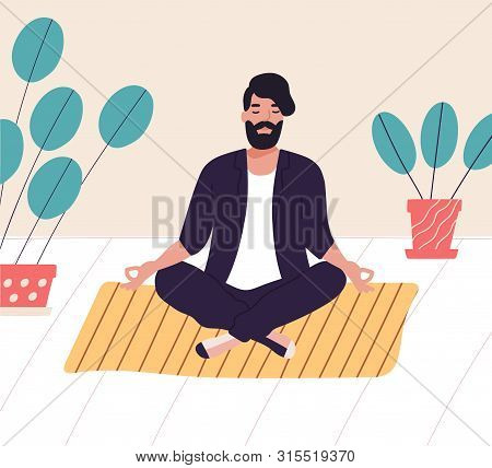 Bearded Man Sitting With His Legs Crossed On Floor And Meditating. Young Man In Yoga Posture Doing M