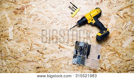 Yellow Screwdriver, Screws, Bits Lie On The Background Of The Osb.