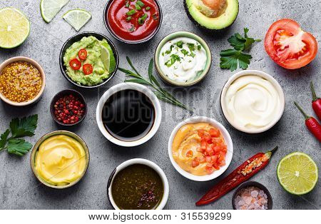 Set Of Different Sauces In Bowls And Ingredients On Gray Rustic Concrete Background, Top View. Tomat