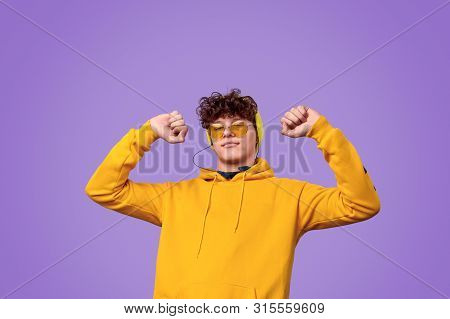 Stylish Youngster In Yellow Outfit Listening To Music In Earphones And Dancing With Clenched Fists A