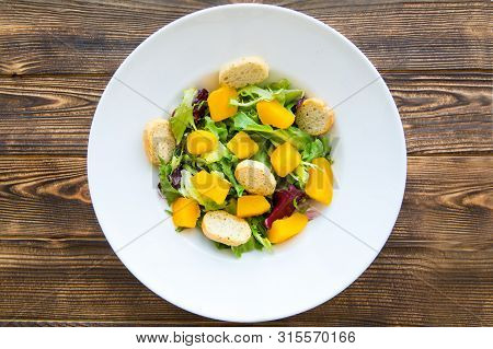 Tasty Pumpkin Salad With Croutons And Greens On Brown Wooden Rustic Table. Top View. Autumn (fall) F