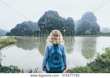 Caucasian Blonde Woman Overlooking Limestone Mountains In Ninh Binh Province, Vietnam