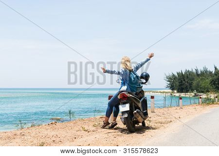 Woman Riding Motorcycle Along The Sea On The Road To Hai Van Pass, Vietnam