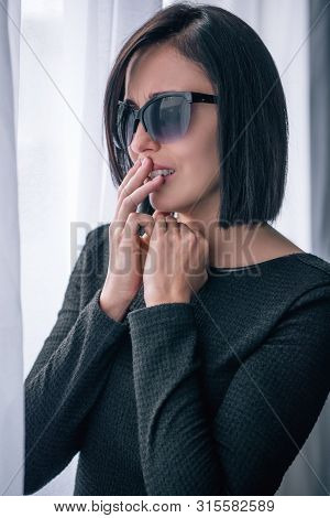 Depressed Brunette Lonely Woman In Sunglasses Covering Mouth And Grieving At Home