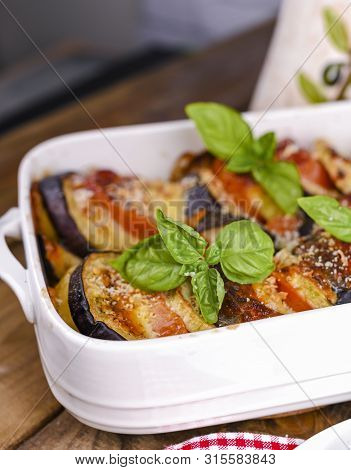 Traditional Italian Food. Baked Eggplant, Tomatoes With Sauce, Parmesan And Basil. Rustic Food For A