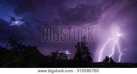 The Moon Peeks Out During A Summer Lightning Storm.
