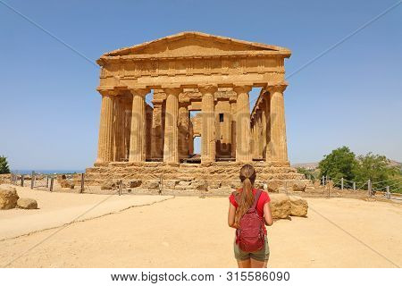 Young Woman Looks At Concordia Temple In The Valley Of The Temples Agrigento, Sicily. Traveler Girl