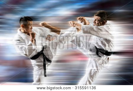 Two martial arts masters, karate practice. on motion background. Blurred effect