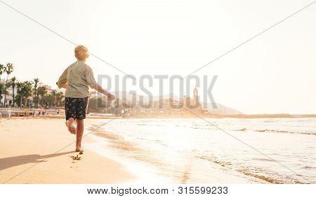 Happy Little Boy Running By Mediterranean Spain Coast In Sitges Town Near Barcelona