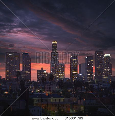 Los Angeles downtown at sunrise. High contrast scene with skyscrapers and palm trees.