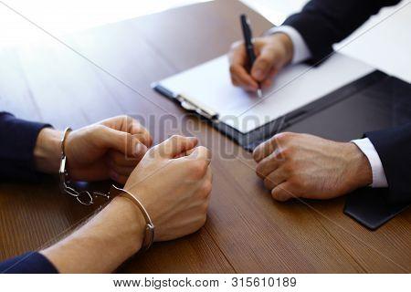 Police Officer Interrogating Criminal In Handcuffs At Desk Indoors