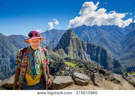 A Male Traveler  Posing At The Inca Ruins Of Machu Picchu, Unesco World Heritage Site In Cusco Regio