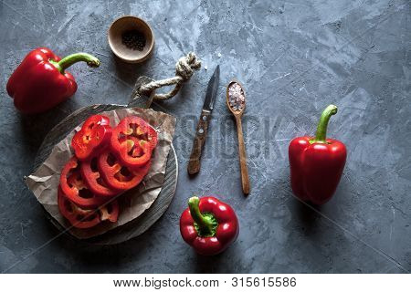 Sliced Sweet Pepper On A Cutting Board With A Knife And Ripe Pepper. A