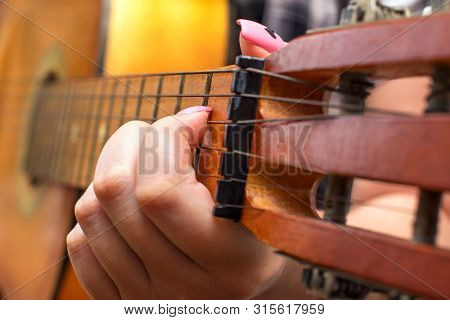 Female Woman Hand Playing Guitar Close Up. Girl Picks A Chord Clamping Frets On The Fretboard