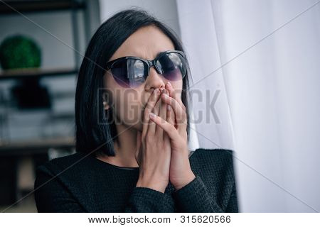 Depressed Lonely Woman In Sunglasses Covering Mouth And Grieving At Home
