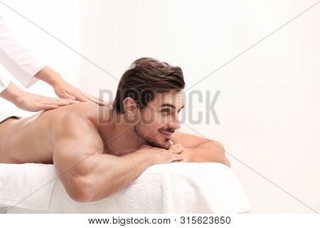 Handsome Young Man Receiving Back Massage On Light Background, Space For Text. Spa Salon