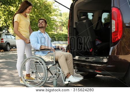 Young Woman Helping Man In Wheelchair To Get Into Van Outdoors