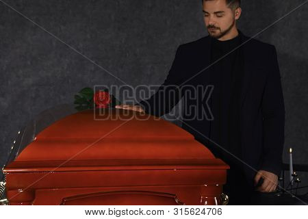 Young Man Near Casket With Red Rose In Funeral Home, Closeup
