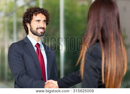Business people handshake outdoor in a modern setting