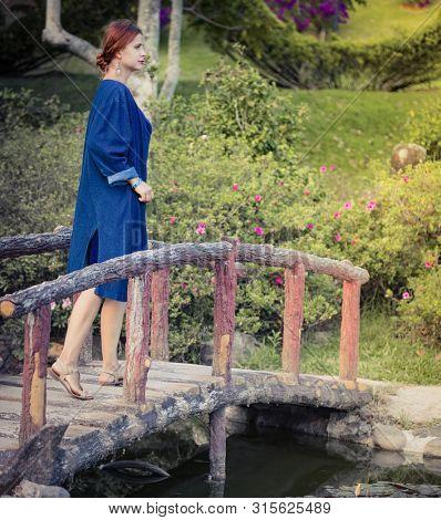 Beautiful woman on a bridge in the flower park, Dalat, Vietnam