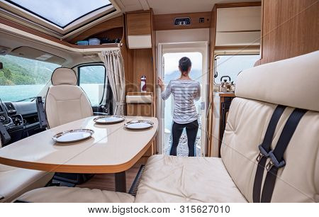 Woman in the interior of a camper RV motorhome with a cup of coffee looking at nature.